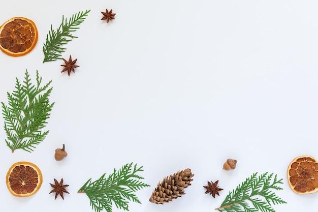 Tannenzweige und sternanis, baumkegel mit trockener zitrusfrucht auf weißem hintergrund, weihnachtsfeiertagshintergrund, flache lage, kopierraum