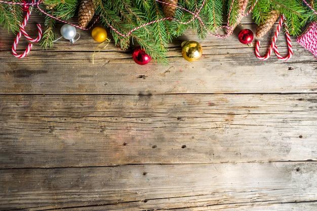 Tannenzweige und weihnachtsschmuck auf hölzernen hintergrund