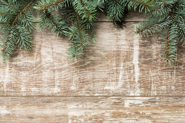 Tannenzweige und weihnachtsschmuck sind auf den brettern ..