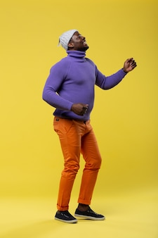 Tanz einfach. freundlicher internationaler freiberufler, der ein lächeln auf seinem gesicht behält, während er in halber position steht