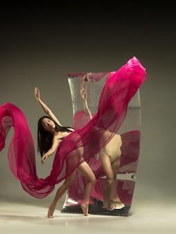 Tanz mit dem feuer. moderne balletttänzerin auf brauner wand mit spiegel. illusionsreflexionen auf der oberfläche. magie der flexibilität, bewegung mit stoff. konzept des kreativen kunsttanzens, der aktion, der inspiration.