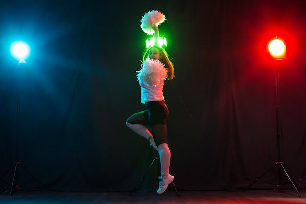 Tanz-, sport-, schönheits- und menschenkonzept - junge cheerleader-mädchen in der dunkelheit zeigen pompons und lächeln.