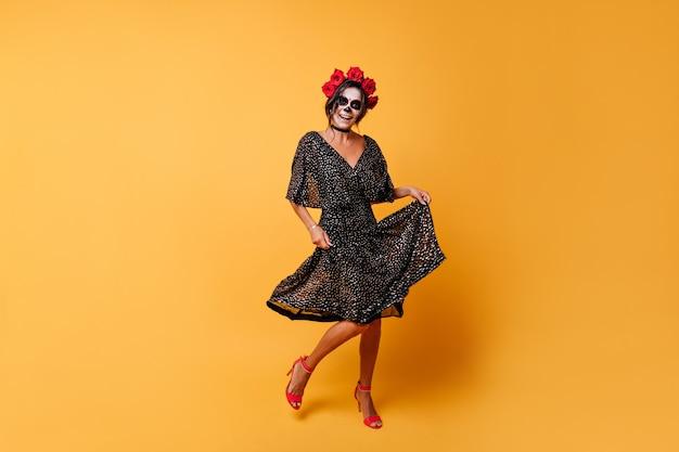 Tanzen aktives mexikanisches modell, das auf orange hintergrund aufwirft. porträt des mädchens in voller länge, das sich über halloween freut.