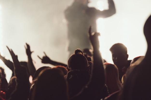 Tanzen bei einem konzert, während der sänger inmitten von lichtern auftritt
