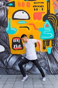 Tanzen des jungen mannes gegen graffitiwand