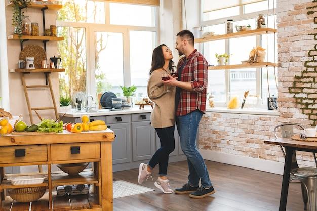 Tanzen in der küche. junges romantisches paar, das verlobungskopienraum feiert. nettes junges paar, das zu hause tanzt und wein trinkt.
