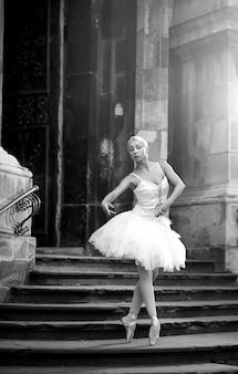 Tanzen ist ihre leidenschaft. atemberaubende ballerina-tänzerin posiert im freien in der nähe eines alten schlosses monochromer weichzeichner