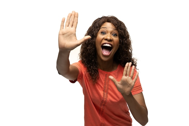 Tanzen. junge afroamerikanerin mit lustigen, ungewöhnlichen volksgefühlen und gesten auf weißem studiohintergrund. menschliche emotionen, gesichtsausdruck, verkauf, anzeigenkonzept. trendiger look, inspiriert von memes.