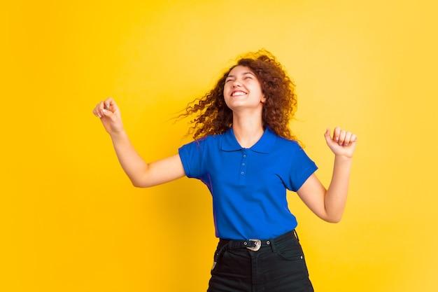 Tanzen mit fliegenden haaren. mädchenporträt des kaukasischen teenagers auf gelbem studiohintergrund. schönes weibliches lockiges modell. konzept der menschlichen emotionen, gesichtsausdruck, verkauf, werbung, bildung. exemplar.
