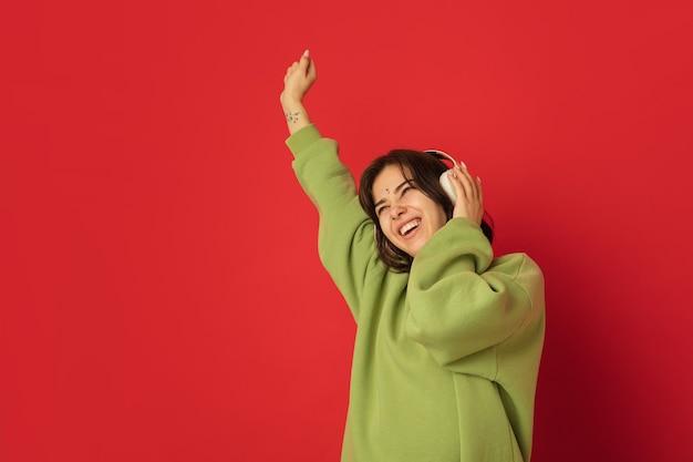 Tanzen mit kopfhörern. porträt der kaukasischen frau auf rote wand mit exemplar isoliert. schönes weibliches modell im grünen hoodie. konzept der menschlichen emotionen, gesichtsausdruck,