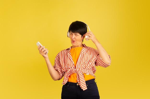 Tanzen. porträt der älteren frau im stilvollen outfit, kleidung lokalisiert auf gelbem studiohintergrund. tech und freudiges älteres lebensstilkonzept. trendige farben, für immer jugend. copyspace für ihre anzeige.