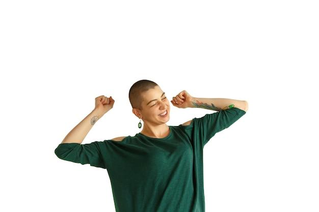 Tanzen. porträt der jungen kaukasischen frau mit ausgeflipptem aussehen auf weißer wand. ungewöhnlicher look mit tattoos und glatze. menschliche emotionen, gesichtsausdruck, verkauf, anzeigenkonzept. jugendkultur.