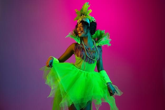 Tanzen. schöne junge frau im karneval, stilvolles maskeradekostüm mit federn, die auf steigungshintergrund in neon tanzen. konzept der feiertagsfeier, festliche zeit, tanz, party, spaß haben.