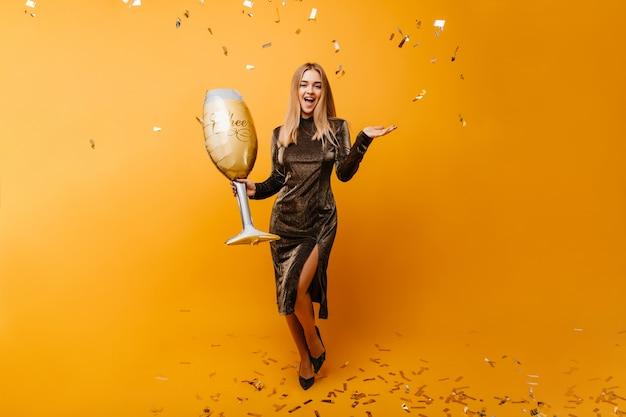 Tanzende ansprechende frau, die auf orange unter cinfetti aufwirft. innenporträt der glamourösen kaukasischen frau mit weinglas, das aufrichtige gefühle ausdrückt.