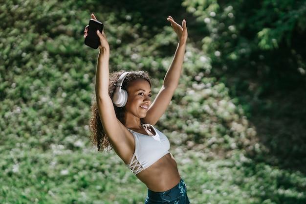 Tanzende athletische frau mit kopfhörern mit ihrem smartphone