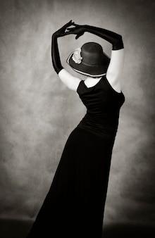 Tanzende frau mit hut und langen handschuhen