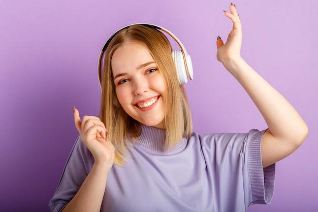 Tanzende frau mit kopfhörern. aktive fröhliche frau tanzt musiklied in kopfhörern hören. teenager-mädchen genießen freizeit-spaß-club-zeit isoliert über lila farbwand