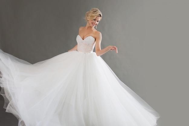 Tanzende junge braut im luxuriösen hochzeitskleid. hübsches mädchen in weiß. gefühle des glücks, des gelächters und des lächelns, grauer hintergrund