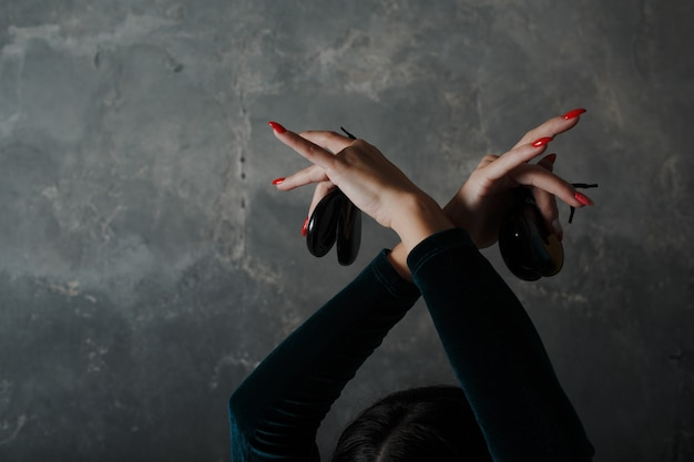 Tanzender flamenco der jungen erwachsenen spanischen frau mit kastagnetten auf grauem weinlesehintergrund