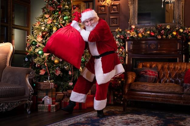 Tanzender weihnachtsmann bereitet sich darauf vor, kindern zu gratulieren. glücklicher weihnachtsmann, der musik hört und mit geschenktüte zu hause nahe dem weihnachtsbaum tanzt.