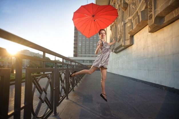 Tanzendes mädchen, das herzförmigen roten regenschirm hält.