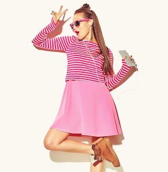 Tanzendes schönes glückliches nettes lächelndes sexy brunettefrauenmädchen in der zufälligen bunten rosa sommerkleidung