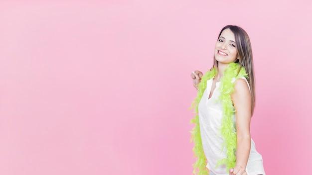 Tanzenfrau, welche die grüne boa steht gegen rosa hintergrund trägt