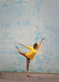 Tanzenhaltung einer frau in der gelben strickjacke