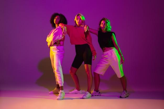 Tanzzeit. stilvolle männer und frau tanzen hip-hop in hellen kleidern auf grünem hintergrund in der tanzhalle im neonlicht.