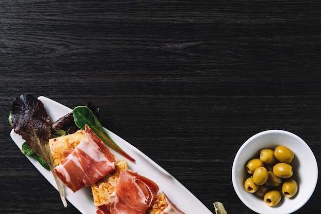 Tapa-omelett und serrano-schinken mit oliven. kopieren sie platz für text