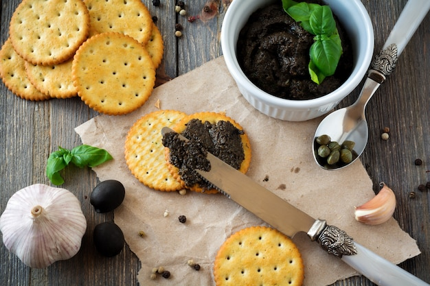Tapenade, traditionelles provence-gericht mit oliven, cracker und basilikum auf einem alten hölzernen tischhintergrund