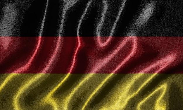 Tapete durch deutschland-flagge und wellenartig bewegende flagge durch gewebe.