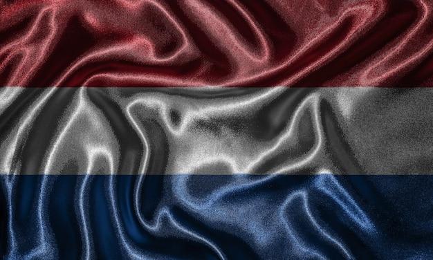 Tapete durch die niederlande-flagge und wellenartig bewegende flagge durch gewebe.