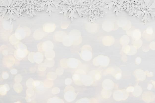 Tapete mit weißen schneeflocken auf weißem holzuntergrund. foto in hoher qualität