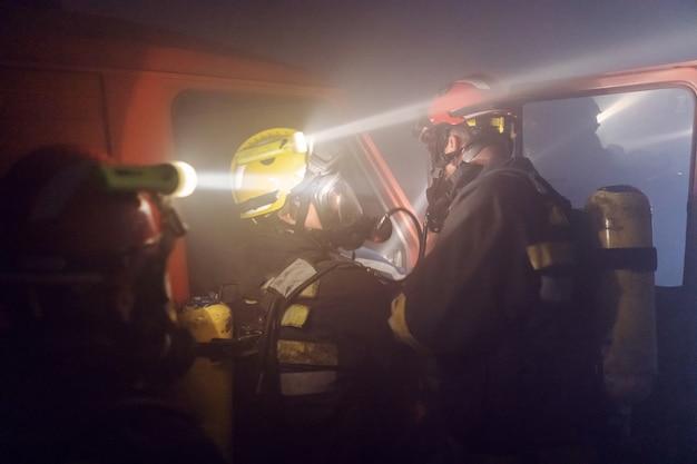 Tapfere feuerwehrleute, die den menschen vom brennenden auto befreien.