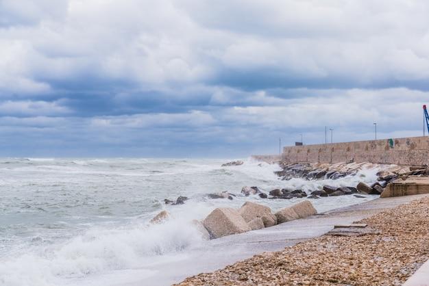 Tapfere wellen des adriatischen meeres schlagen gegen den wellenbrecher der seeseite in bari, italien