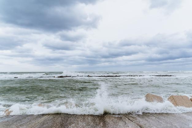 Tapfere wellen des adriatischen meeres schlagend gegen den wellenbrecher der seeseite in bari, italien