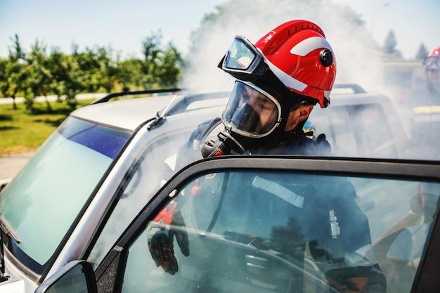 Tapferer feuerwehrmann, der in feuer ins auto steigt und versucht, opfer eines pflegeunfalls zu retten.