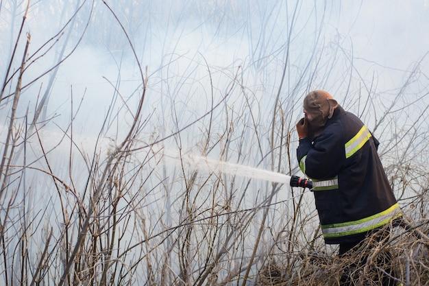 Tapferer feuerwehrmann steht im rauch, kämpft wildes feuer in der landschaft