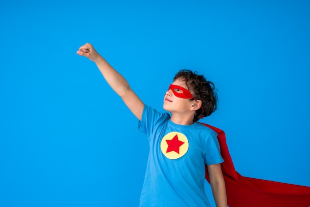 Tapferer junge in einem superheldenkostüm mit rotem umhang und maske streckte die hand aus