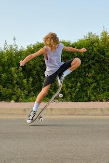 Tapferer junge springt mit skateboard