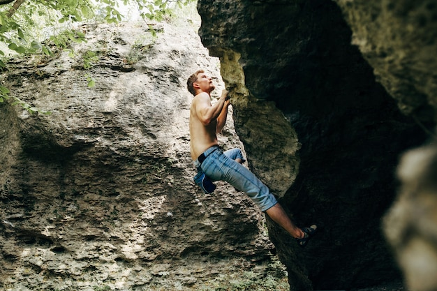 Tapferer junger mann klettert die klippe