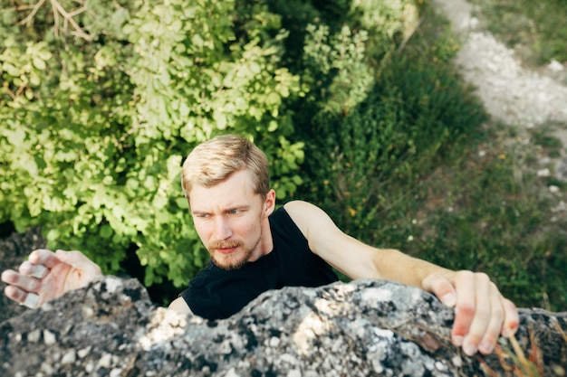 Tapferer junger mann klettert die spitze der klippe