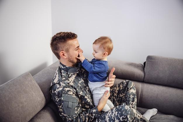 Tapferer soldat, der mit seinem geliebten sohn auf dem sofa sitzt und mit ihm spielt.