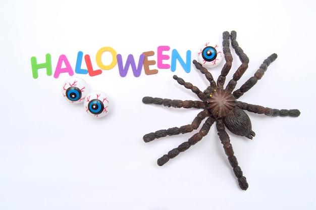 Tarantulaaugen und farbige buchstaben, die das wort halloween bilden