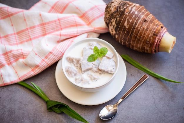 Taro-essen mit dessert-taro gekocht mit zucker und kokosmilch auf schüssel und frischer roher bio-taro-wurzel kochfertig, asiatisches thailändisches essen