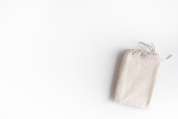 Tarockplattform-baumwolltasche mit beschaffenheitspapierblättern auf weißem hintergrund