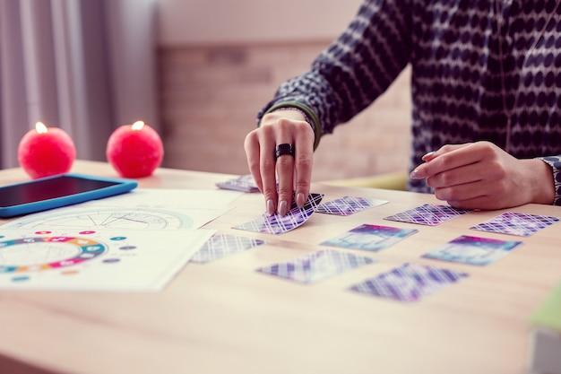 Tarot-karten. schließen sie oben von einer karte, die von einer intelligenten professionellen wahrsagerin geöffnet wird