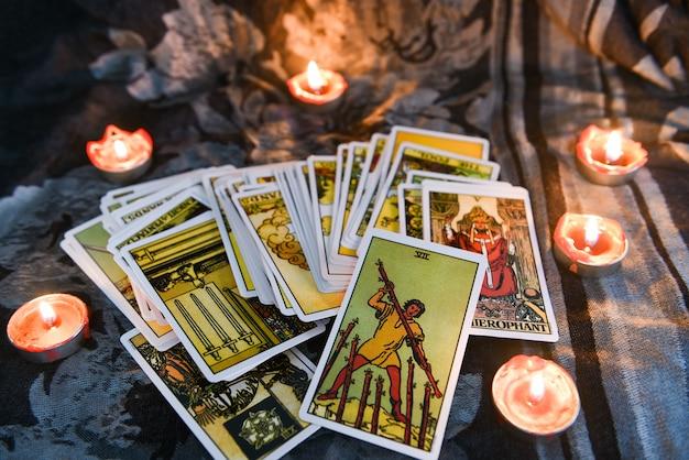 Tarotkarte mit kerzenlicht auf dem dunkelheitshintergrund für astrologie okkulte magische illustration - magische geistige horoskope und palme, die wahrsagerkonzept lesen