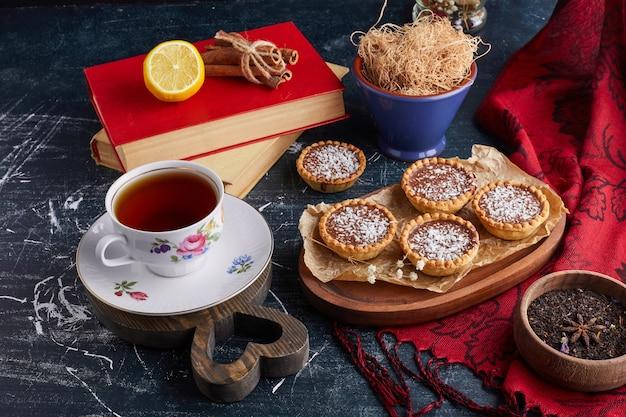 Tartalettes mit schokoladenfüllung und kokosnuss mit einer tasse tee.